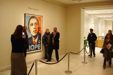 People taking photos of themselves standing next to Obama portrait
