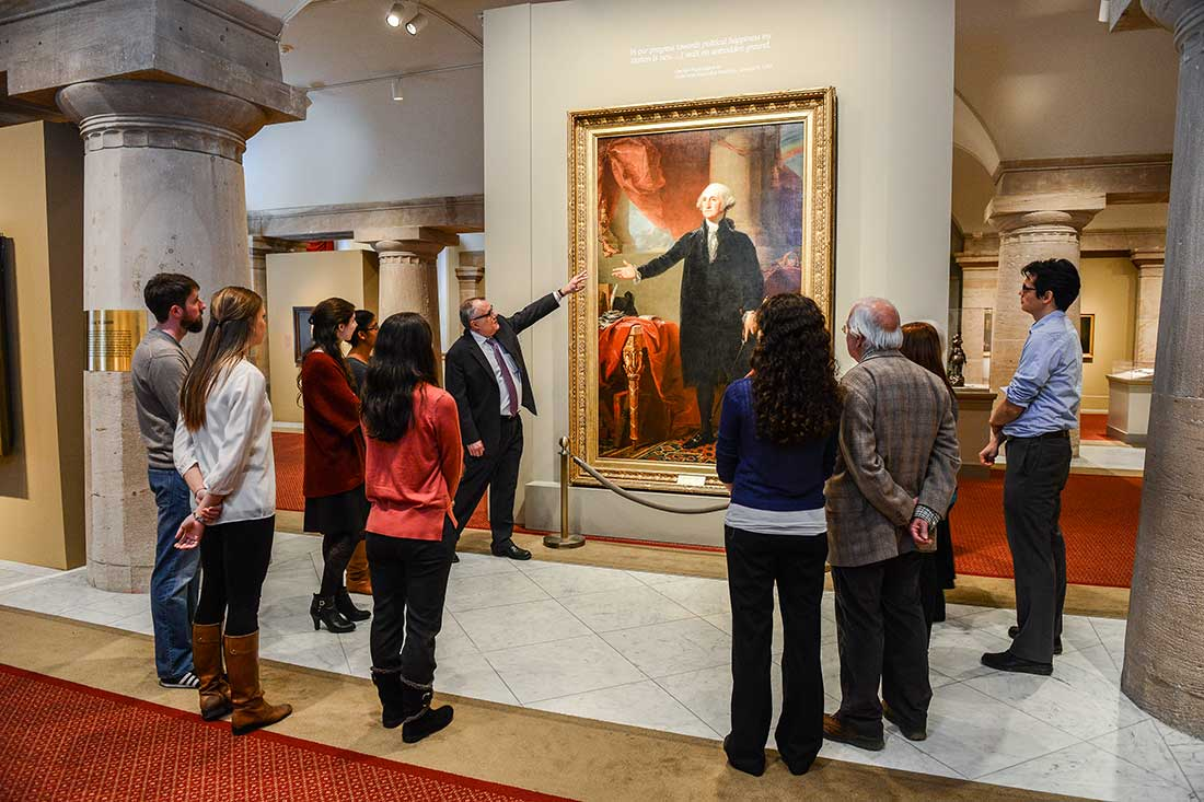 A curator led-tour in the museum galleries, with the curator pointing at painting of George Washington