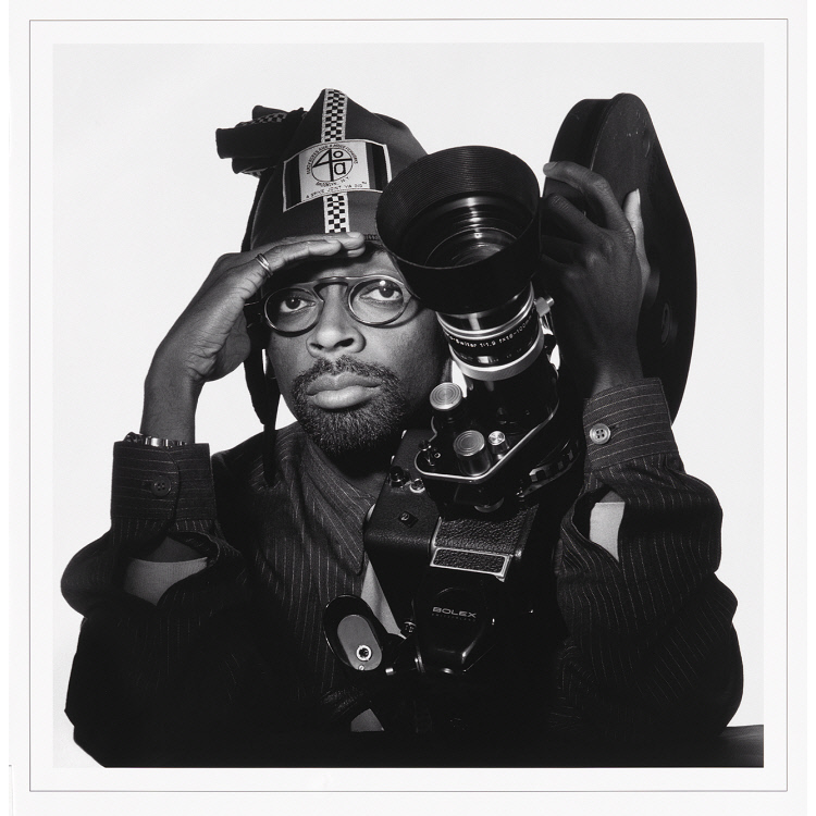 Black and white photo of Spike Lee holding film camera, with his right hand shielding his eyes as if from a bright sun