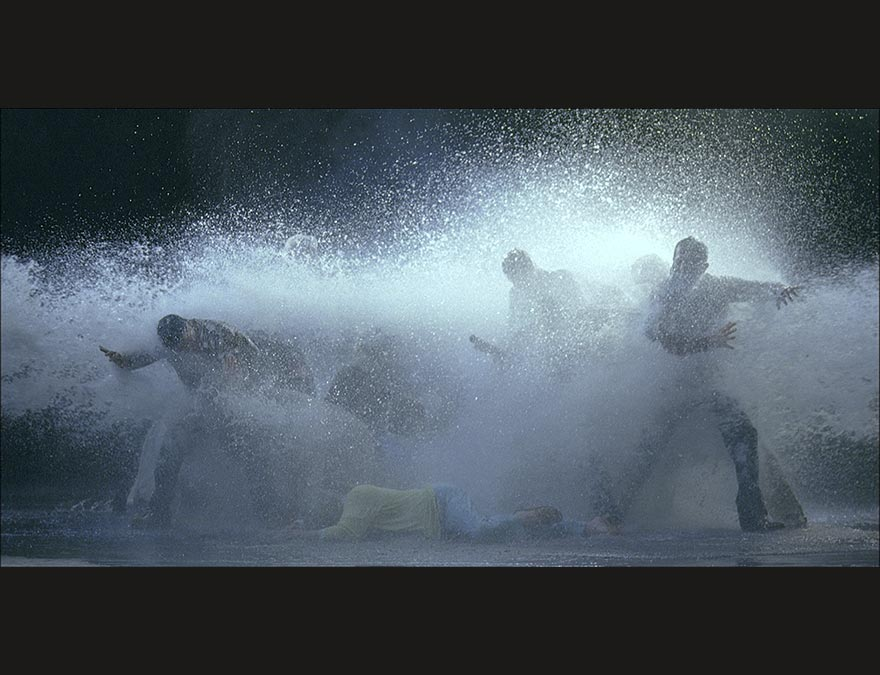 Groupl of people being sprayed with powerful hoses of water from several angles