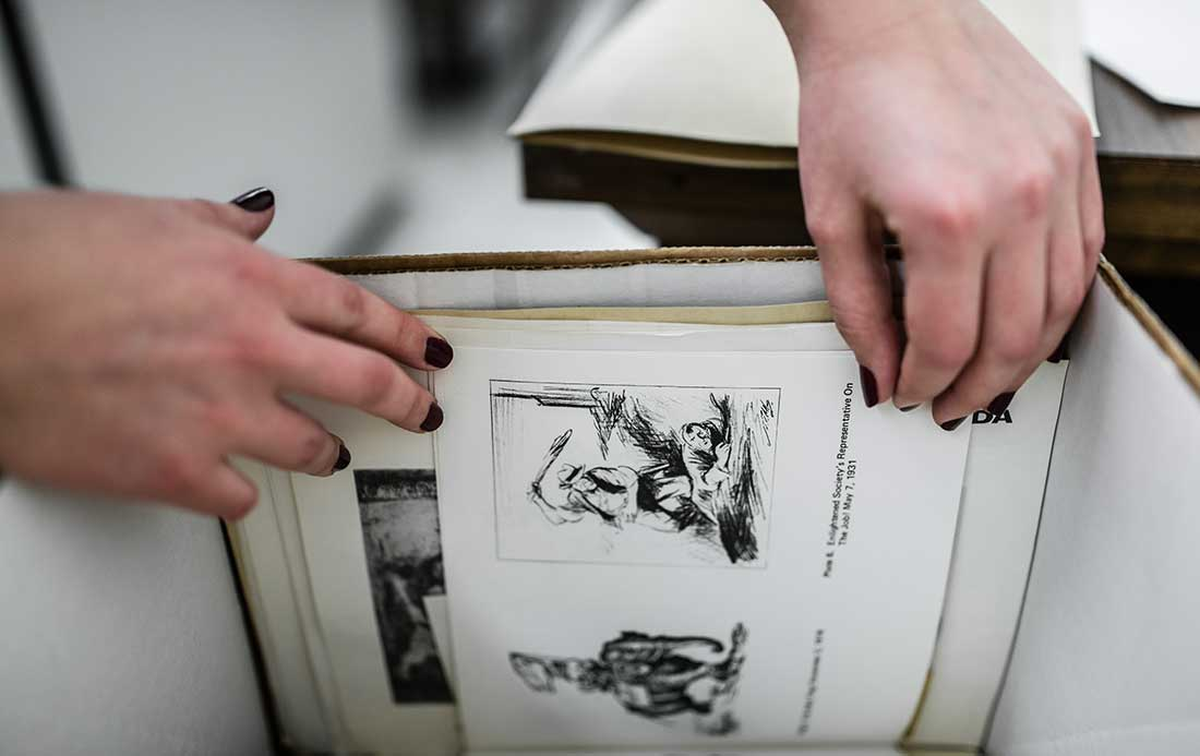 A researcher paging through a box of primary source documents relating to portraiture and history