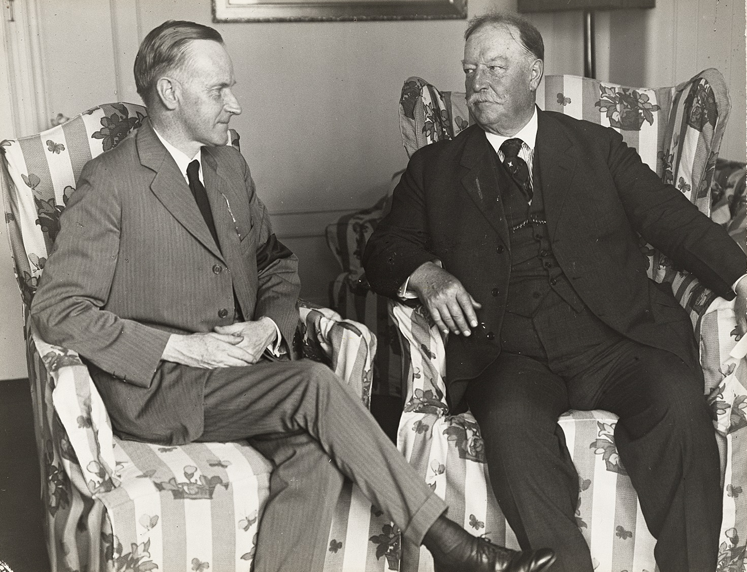 Two men sitting in flowered armchairs engaged in conversation