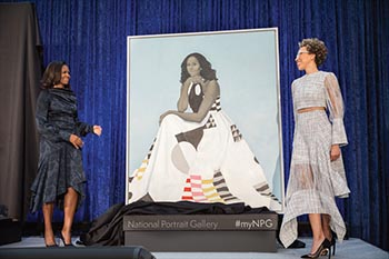 two women standing near an unveiled portrait