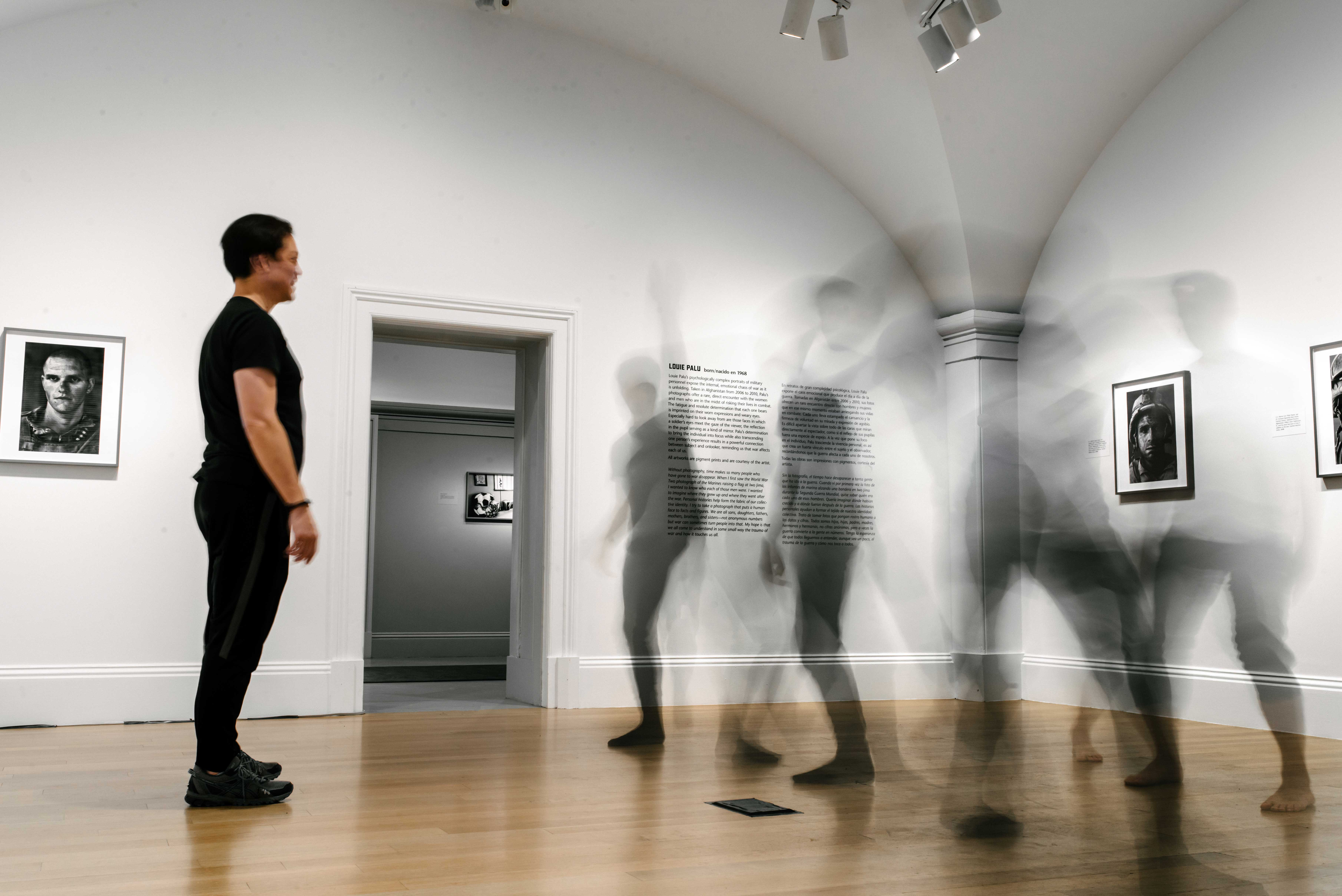 Image of a man standing in a gallery looking at three moving shapes