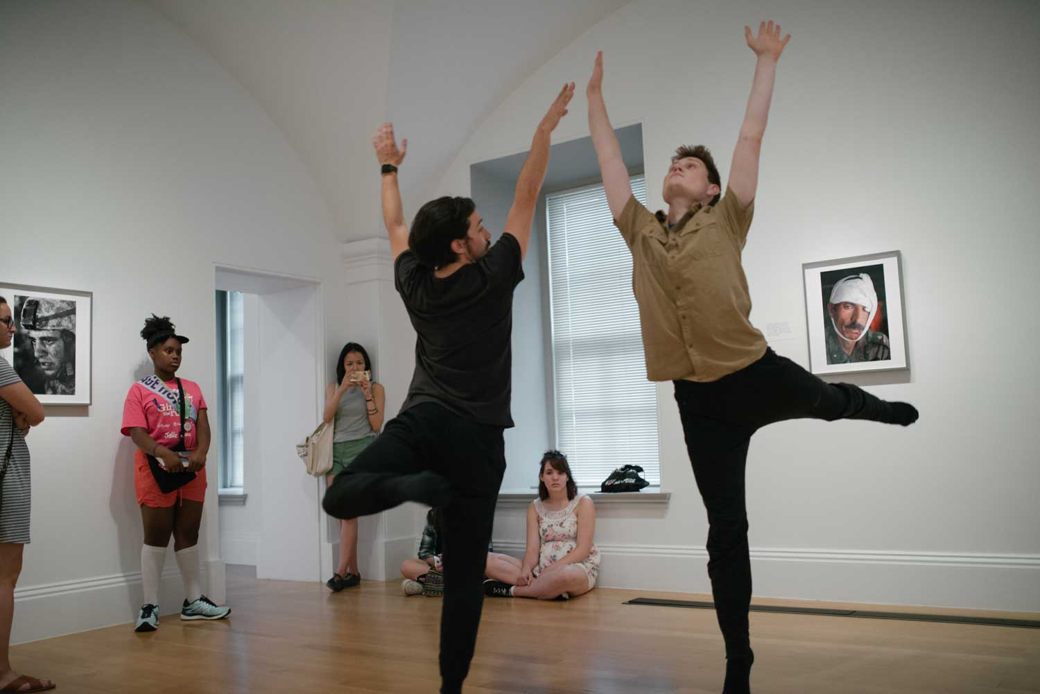 Two men dancing with their arms up in an art gallery