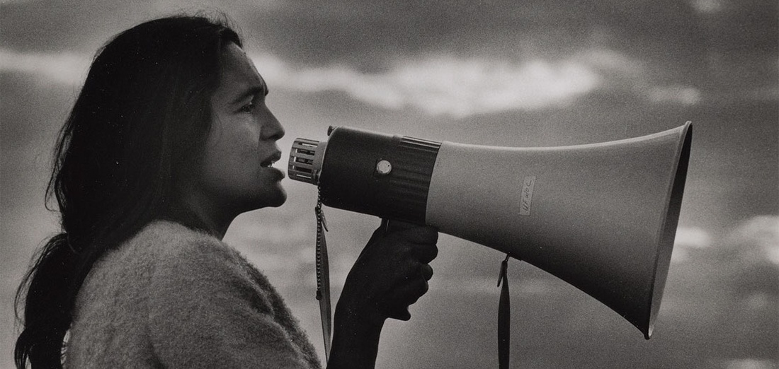 Black and white photo of Dolores Huerta holding a bull horn