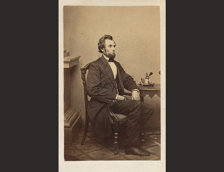 Photograph of Abraham Lincoln seated at a small desk