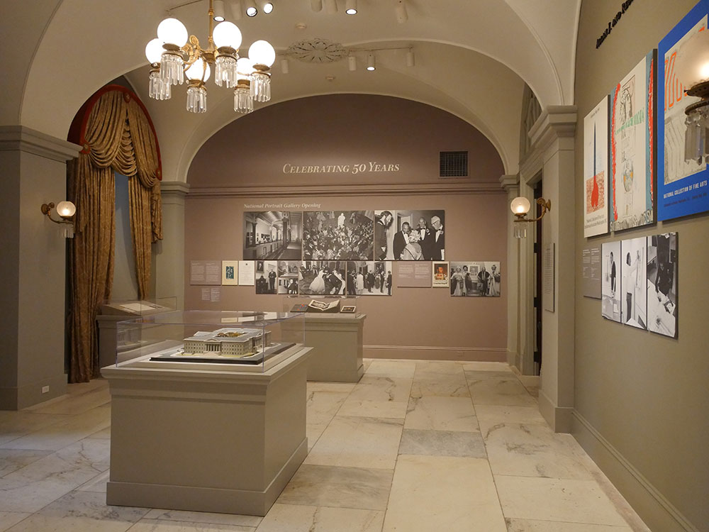 view of the exhibition, with posters and black and white photographs on the walls