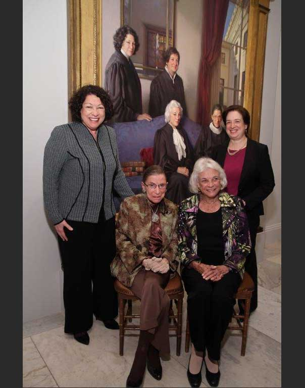 Supreme Court justices standing in front of the painting representing them