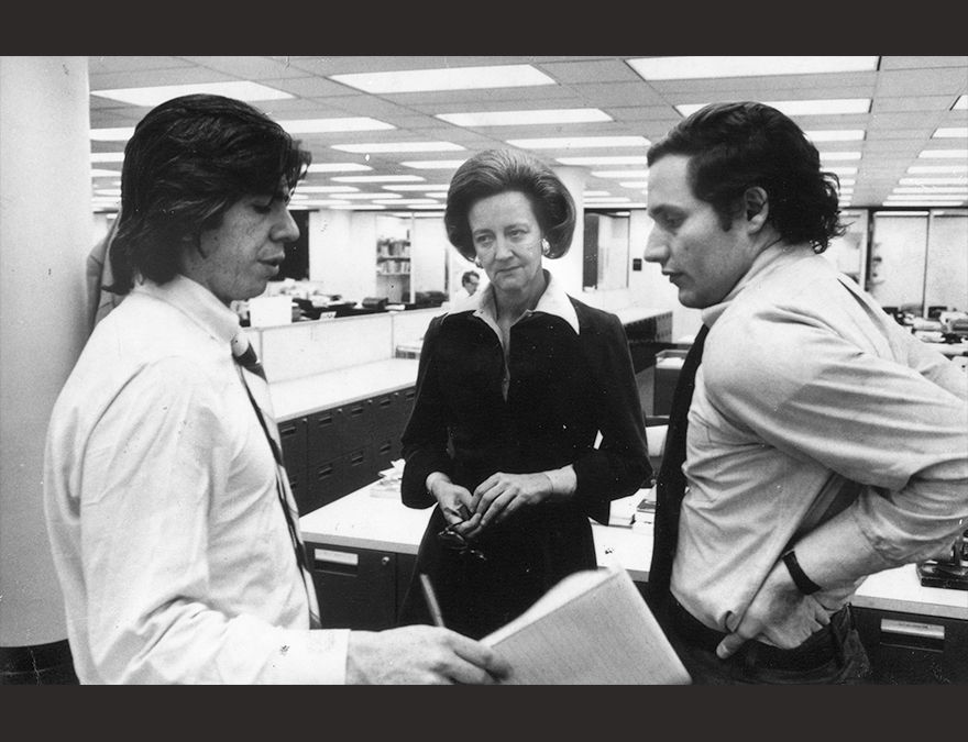 Black and white photo of Katherine Graham in news offices with Carl Bernstein and Bob Woodward