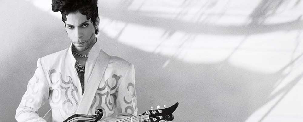 Black and white photo of Prince holding a guitar