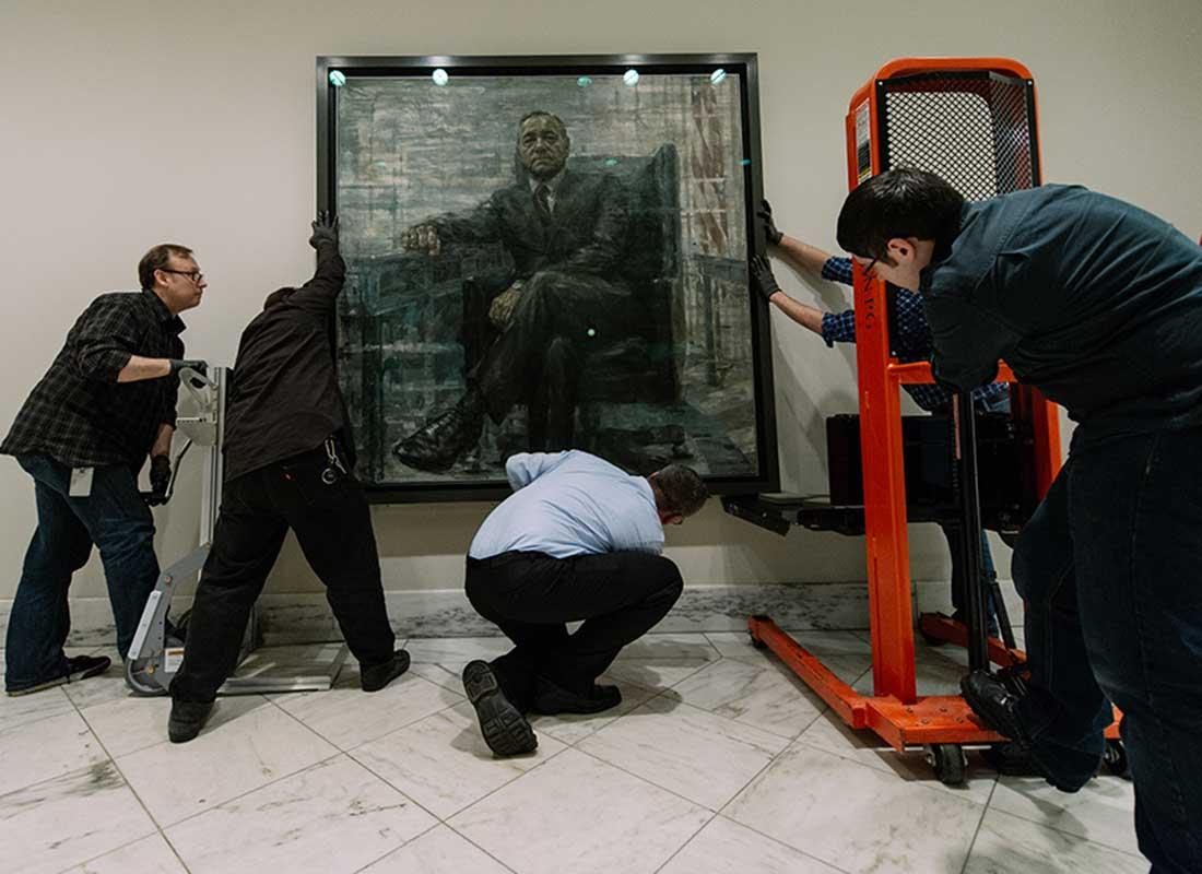 Manipuladores de obras de arte instalando el retrato en la Galería de Retratos