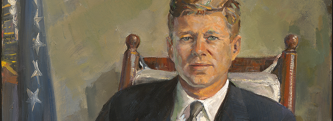Portrait of a man (John Kennedy) seated in a rocking chair with a flag to his right.