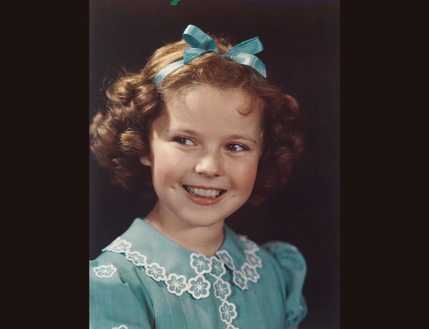 Little girl in a blue dress with a blue bow in her hair