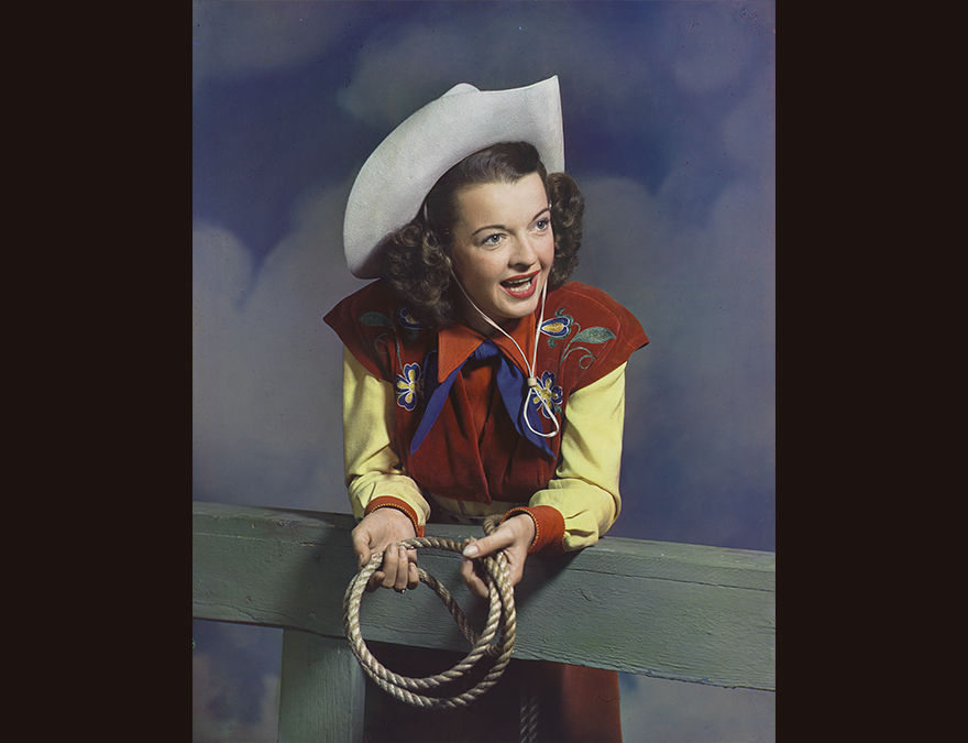 Woman in a cowgirl outfit leaning on a fence