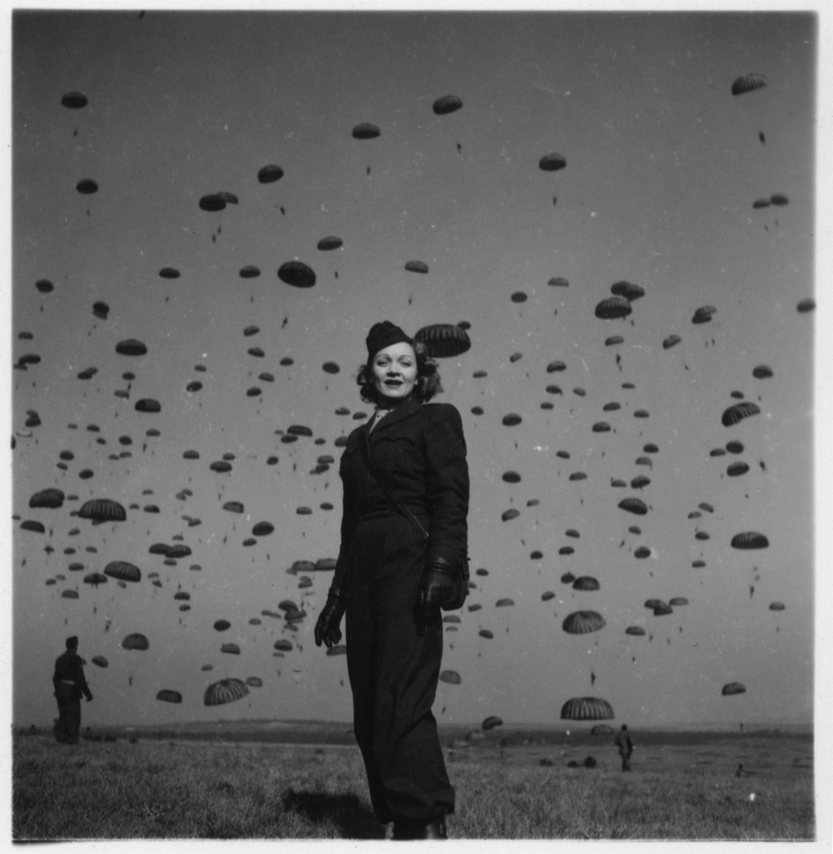 Black and white image of a woman in an army uniform with hundreds of paratroopers in the background