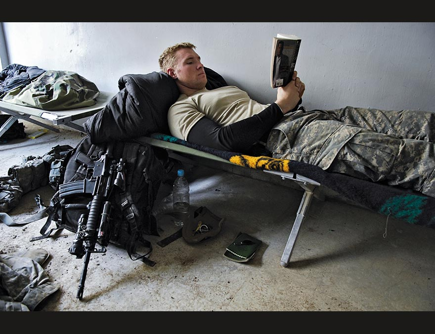 Young soldier reading on a cot