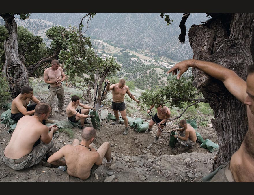 Shirtless soldiers gathering on the side of a mountain