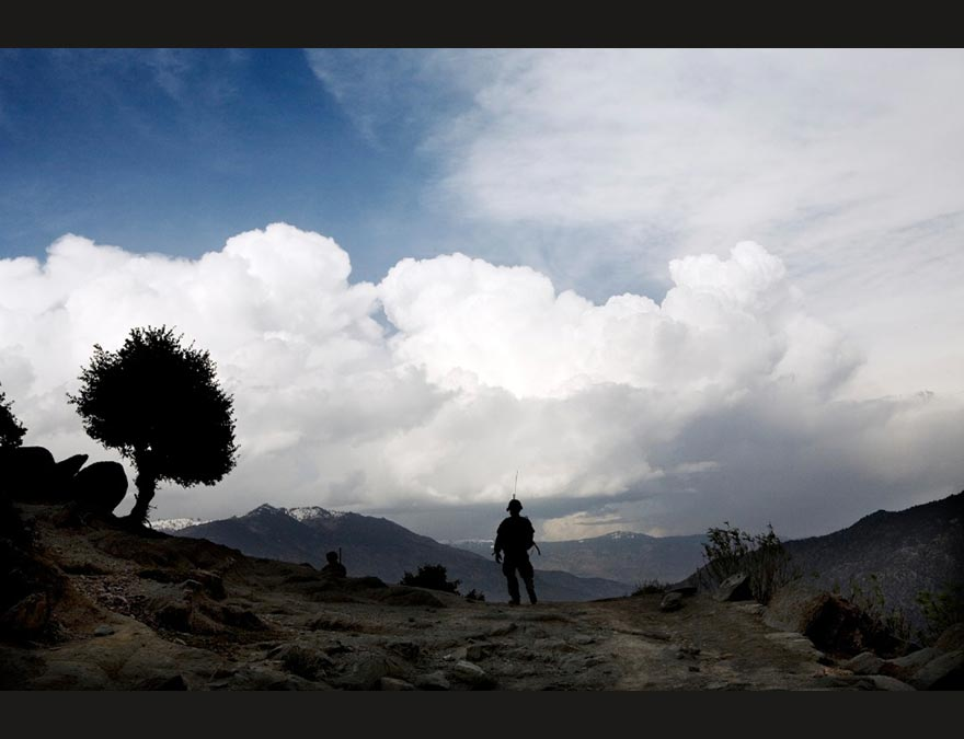 Man silhouetted against a landscape with a tree and clouds