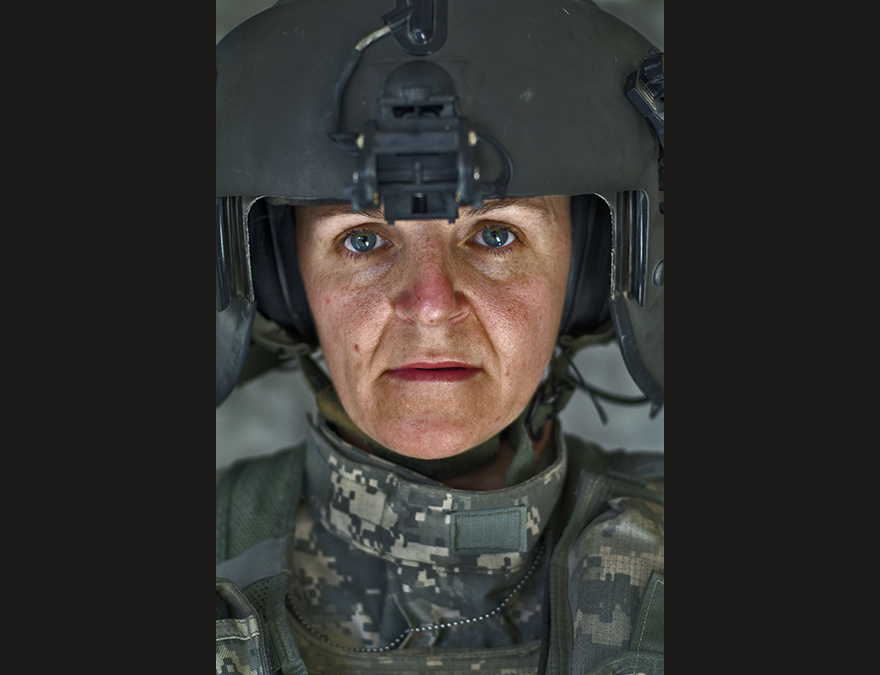Female heliocopter pilot in fatigues and large helmut
