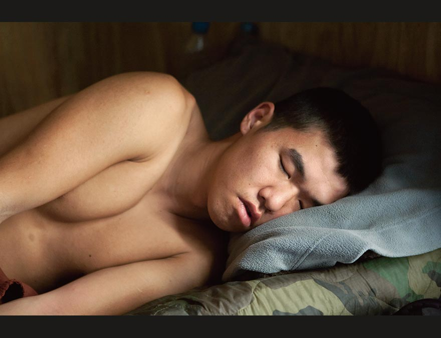 Young soldier asleep on a cot