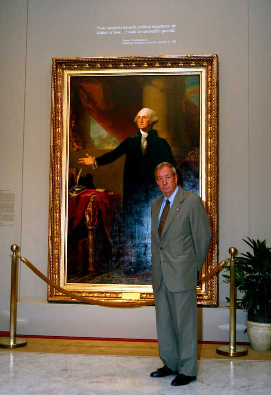 Photograph of a man standing in front of a portrait of George Washington