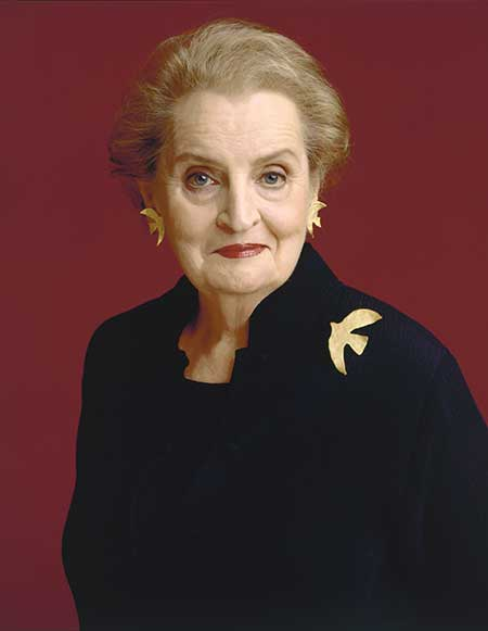 Photograph portrait of Madeleine Albright, looking straight into camera, wearing black with a gold pin of bird on her shoulder