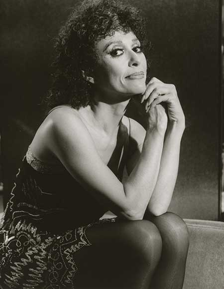 Black and white photo of Rita Moreno, sitting and looking towards camera