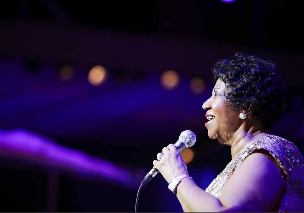 Aretha Franklin cantando con un micrófono
