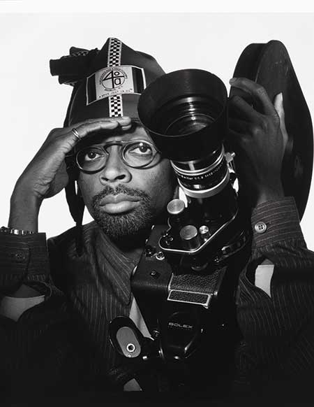 Black and white photo of Spike Lee, with film camera