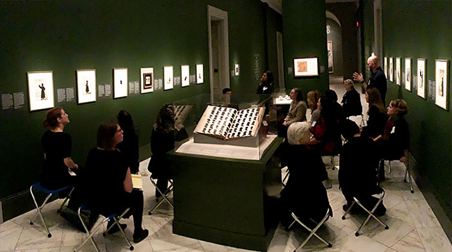 group of people listening to a lecture in a gallery