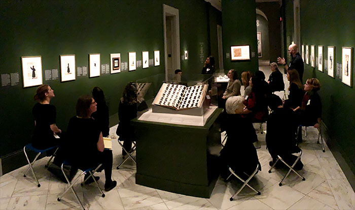 group of people sitting in a lecture in an exhibition