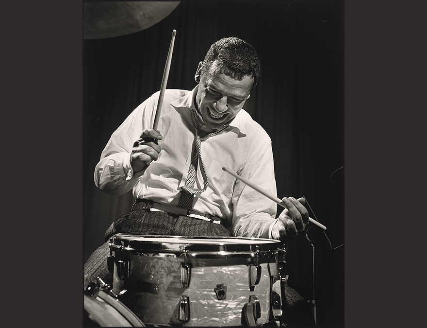 Photograph of a man at a drumset--drumming rapidly