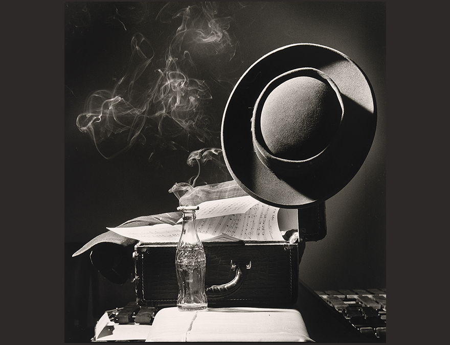 Photo of a hat, sheet music and a burning cigarette