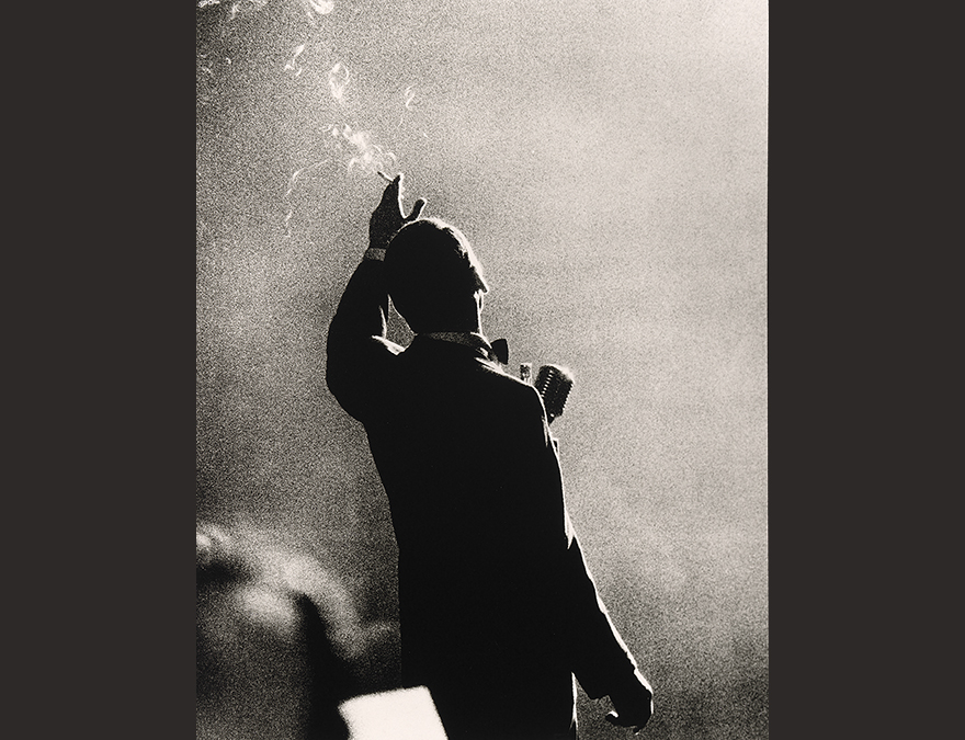 Silhouette of a man facing the audience singing in a smoke-filled room