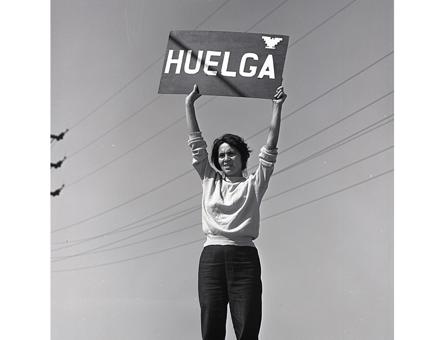 "Woman holding a sign above her head that reads"" STRIKE"" in Spanish"