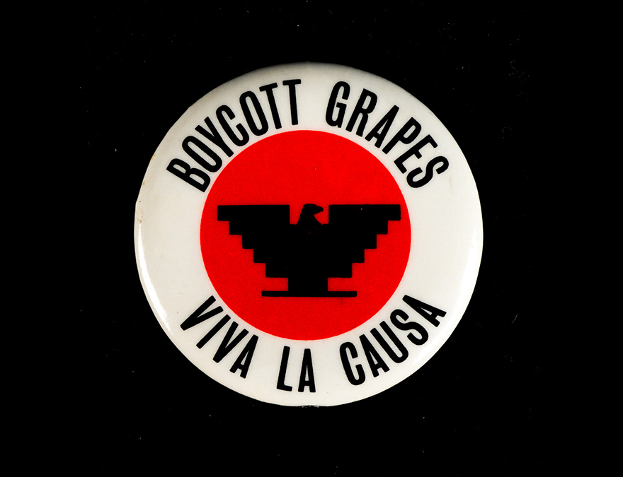 "A ""Boycott Grapes"" pin with a white border and red center featuring a stylized eagle"