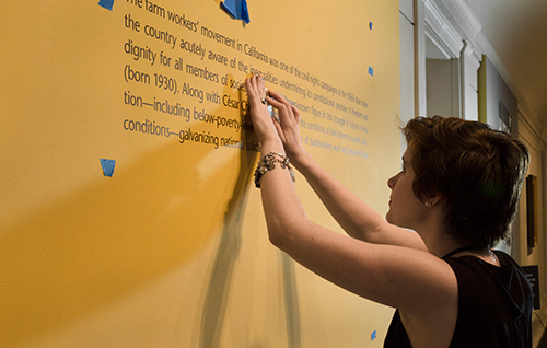 Intern installing an exhibition, and putting up wall text