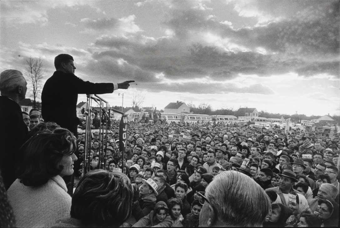 Black and white image of a man standing on a podium and pointing his finger at a very large crowd while speaking