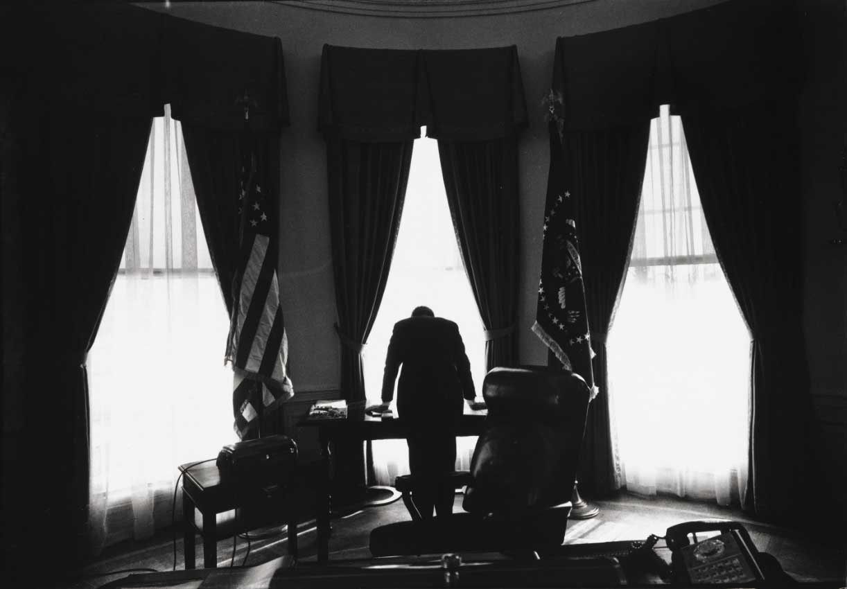 Black and white photo of the White House oval office with the sihouette of a man facing away from the camera in the frame of a window