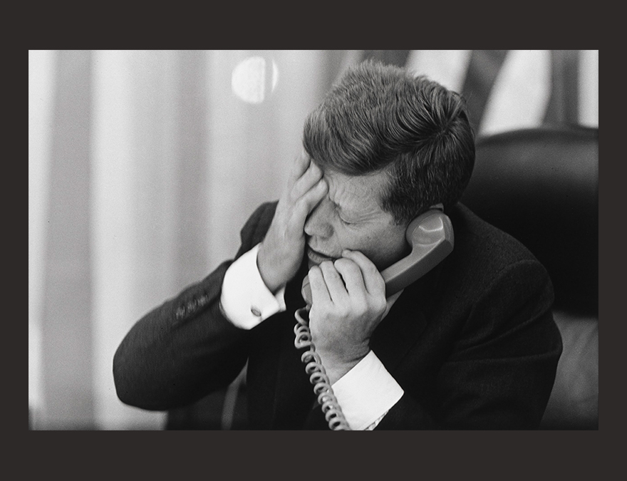 a man rubbing his face while on the phone