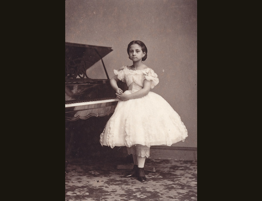 little girl in a white dress standing by a piano