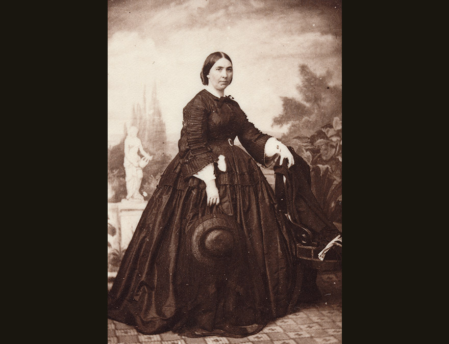19th century woman in a long dark dress standing against a landscape
