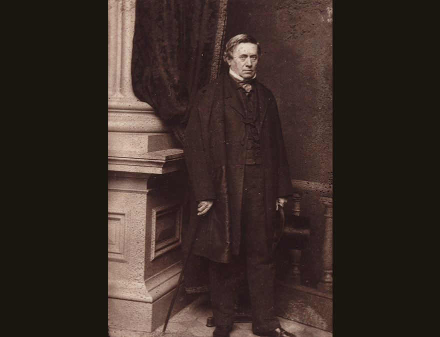 19th century man in a suit standing by a column