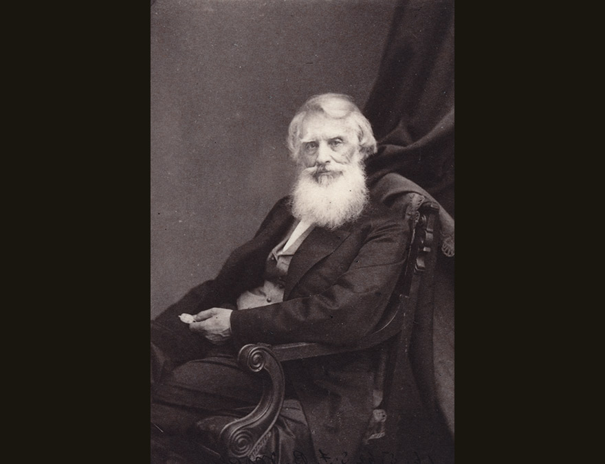 19th century man with white hair and a beard seated in a chair