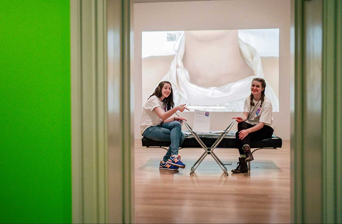 Two teens in the museum galleries, presenting a video portrait of musician Esparanza Spalding