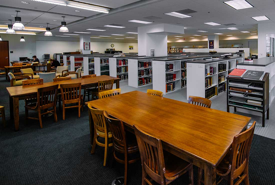 View of library reading room, showing tables and chairs, and bookshelves