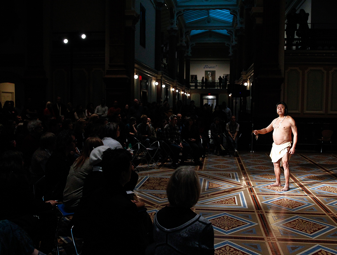 Bare-chested man standing in a spotlight in the Great Hall