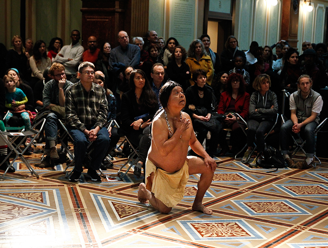 Man in Native American dress kneeling in the Great Hall