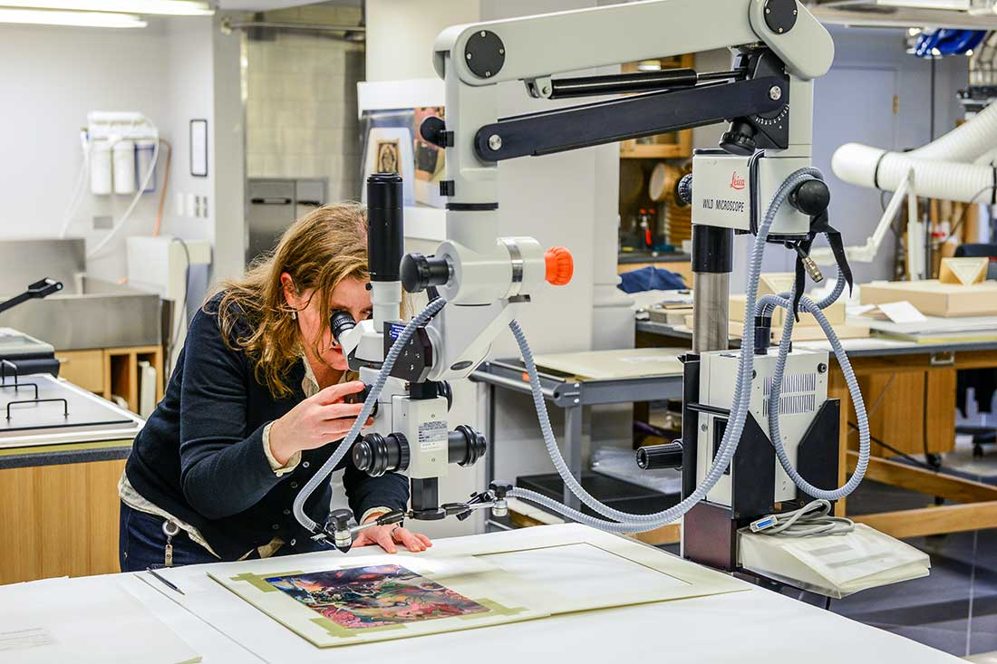 Conservator working, using a microscope